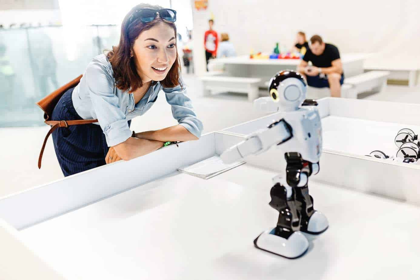 Young adult woman looking at the toy robot - geek gift idea